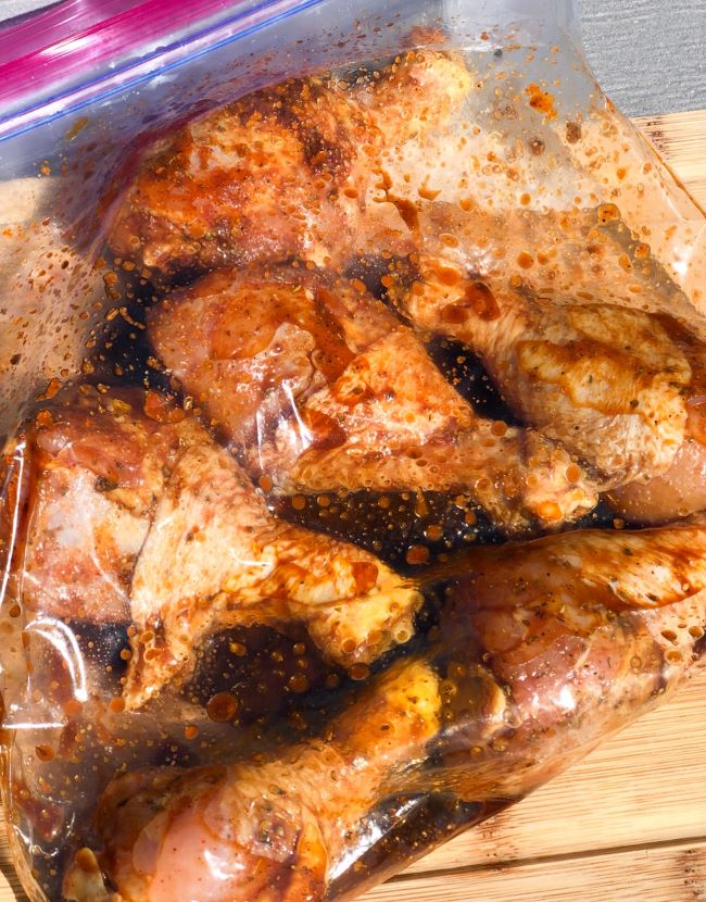 chicken drumsticks mixed with seasonings inside of freezer bag