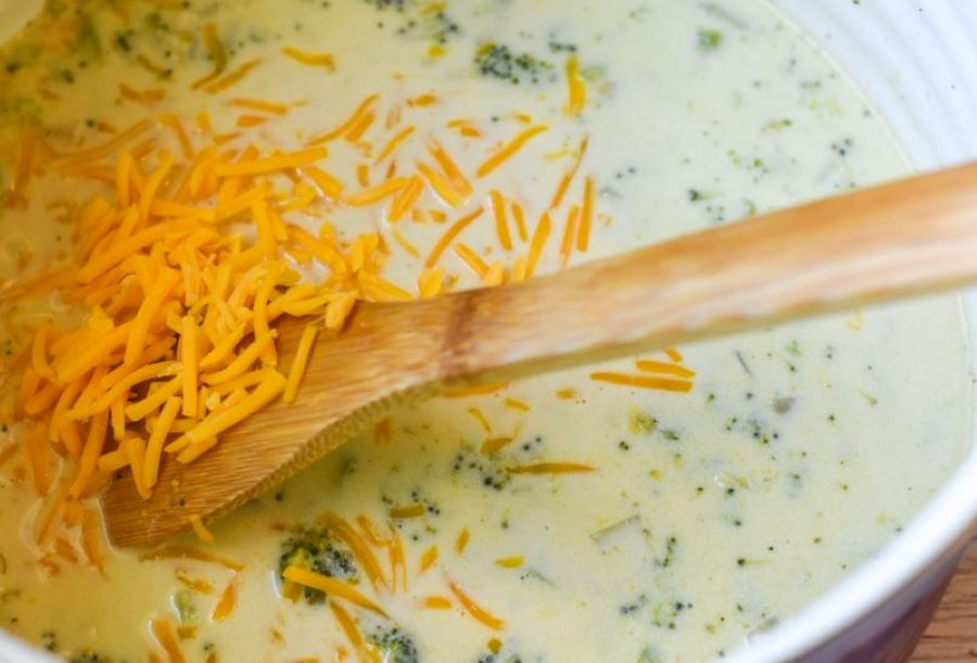 shredded cheese being added to pot with broccoli cheese soup