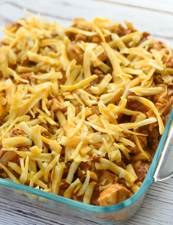 enchilada casserole mixture spread into pan topped with shredded cheese