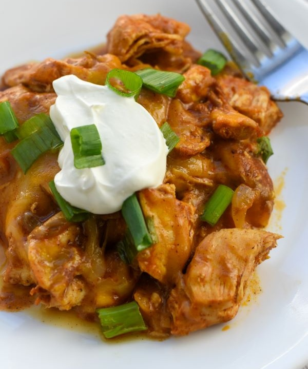 chicken enchilada casserole topped with green onions and sour cream on white plate