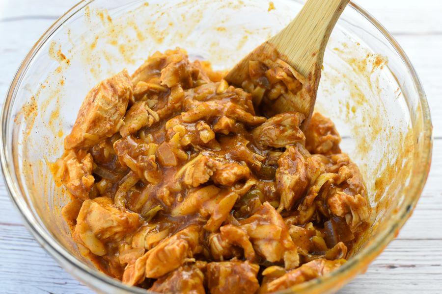 chicken enchilada casserole filling mixture in glass bowl