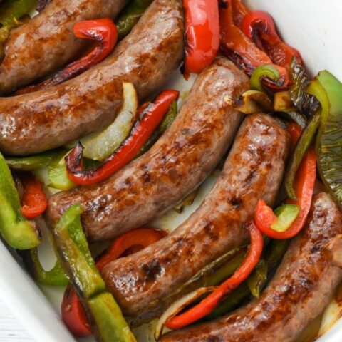 cooked brats in white casserole dish with peppers