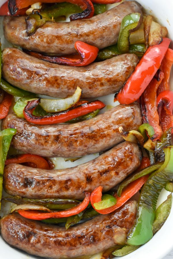 brats in white casserole dish with peppers